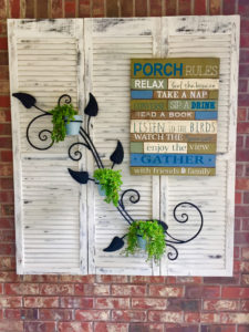 repurposed-shutters-hung-on-brick-wall-with-art-and-iron-planter