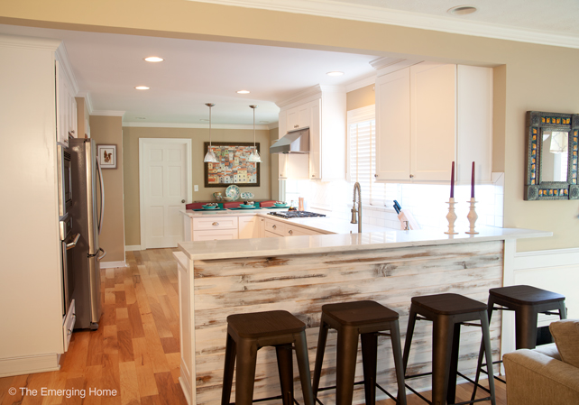 View from the family room into the kitchen shows the wall removed and a counter bar with tall stools in its place.