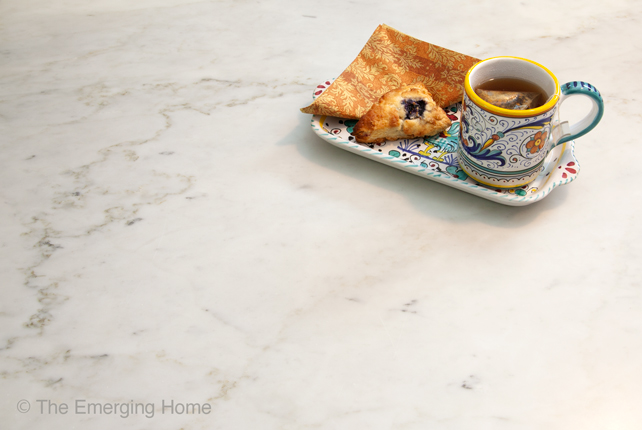 A colorful Italian plate holds a cup of tea and a scone as it sits on a dark veined section of the white marble countertop.