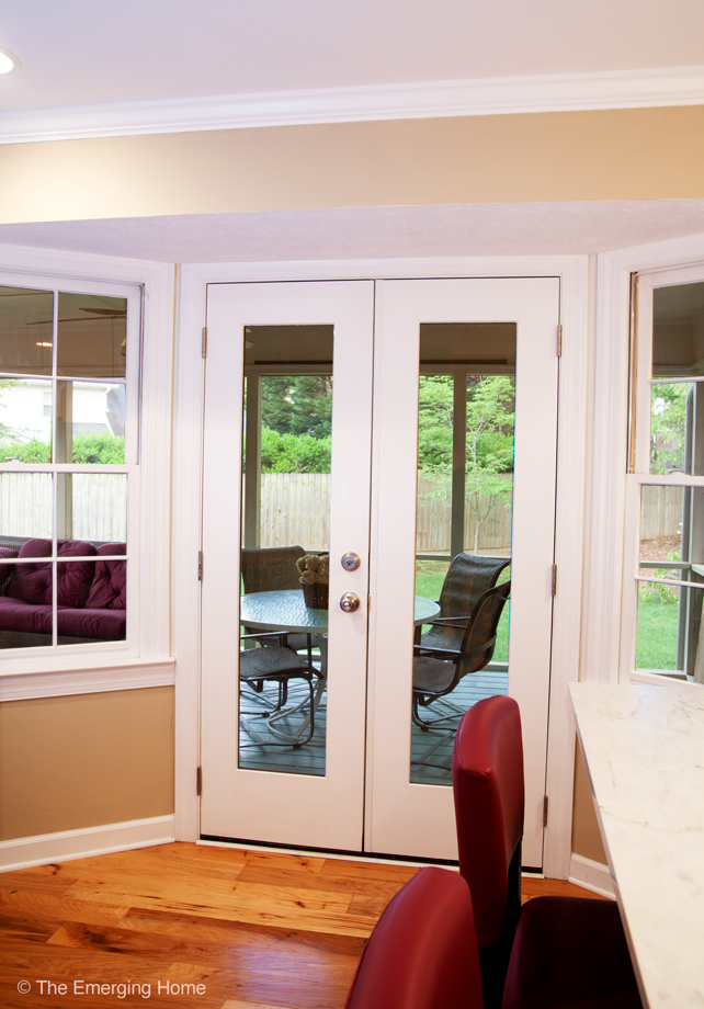 Double French style doors have been installed in place of a solid square window. New doors allow access to seating and eating area on screen porch.