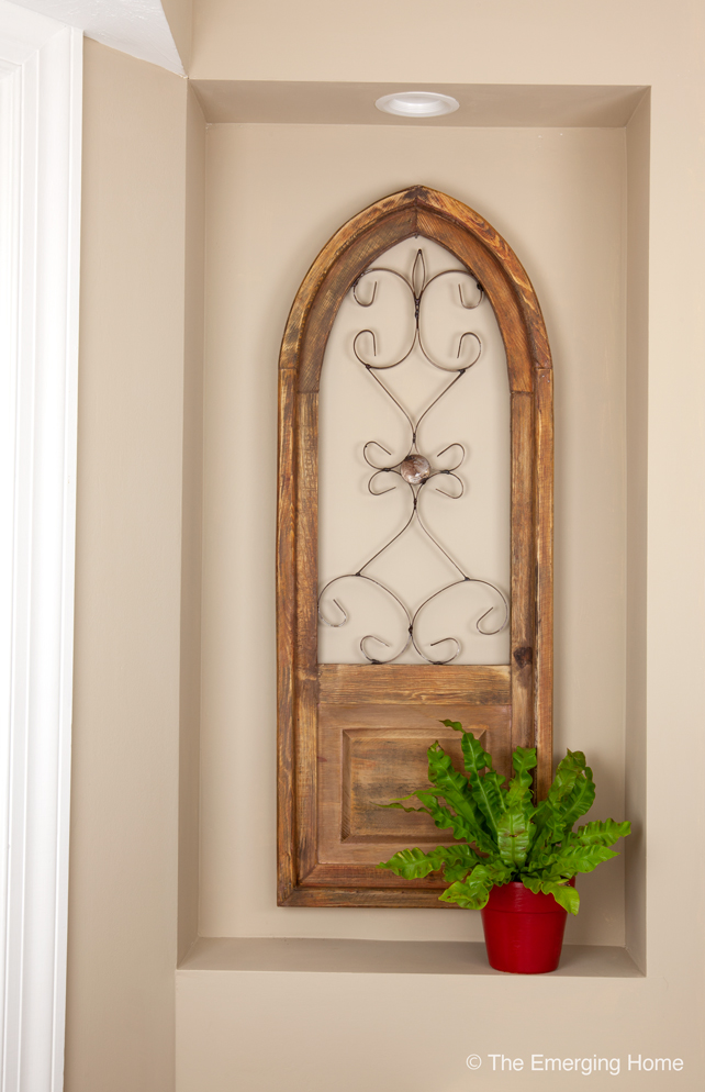 The natural wood art piece with a decorative metal inset hangs in the  niche in the kitchen. A red planter holds a small houseplant.