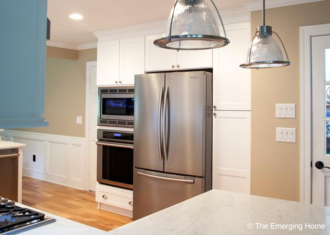 Two door, vertical, pantry cabinet is installed beside refrigerator