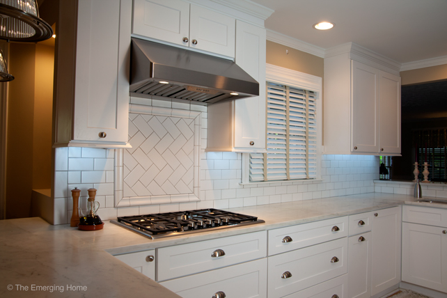 Long counter of top and lower white kitchen cabinets topped with marble. Electrical outlets are placed under top cabinets in order to allow uninterrupted subway tile backsplash.