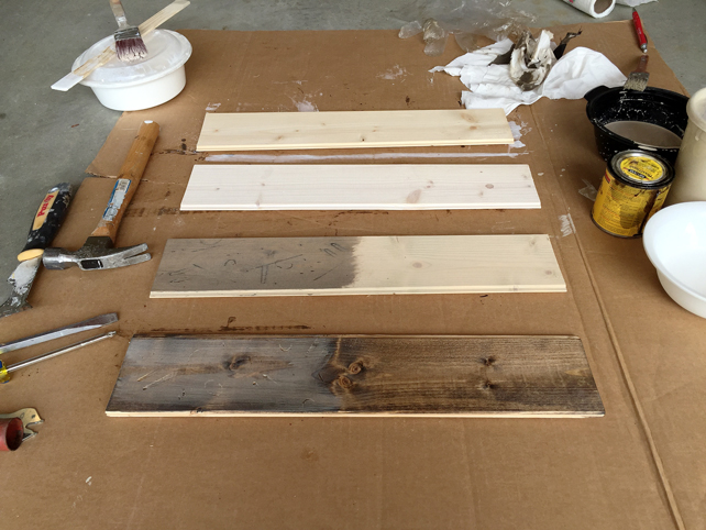 4 short wood plank pieces covered with samples of whitewash and walnut stain