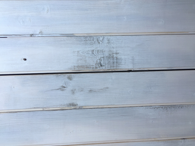 finished whitewashed planks sanded to reveal dark stain beneath paint shows rustic effect