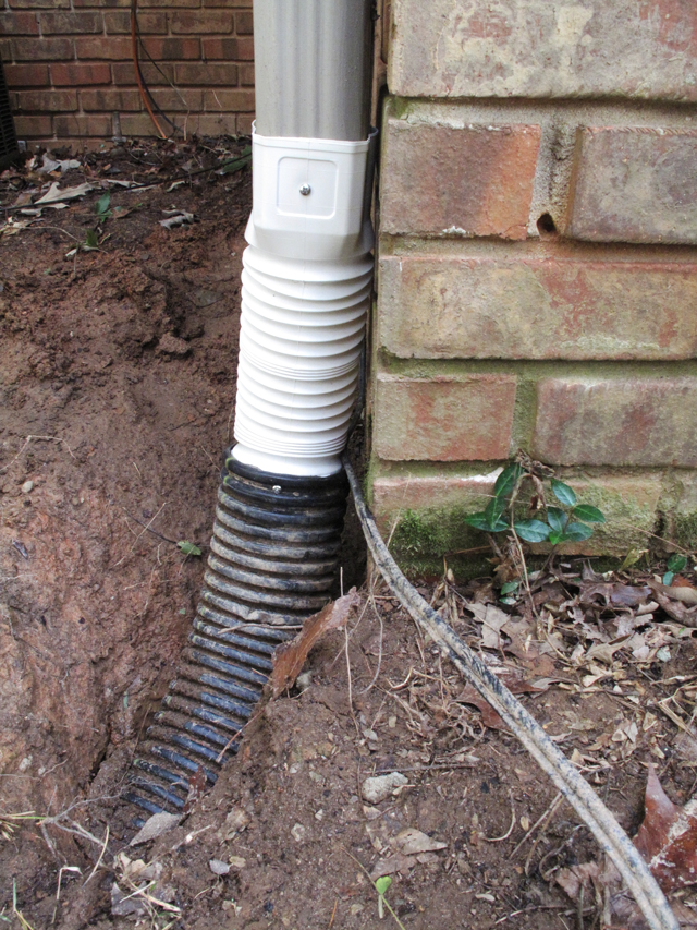 Metal downspout, white plastic downspout adapter and black flexible drainpipe and secured with screws