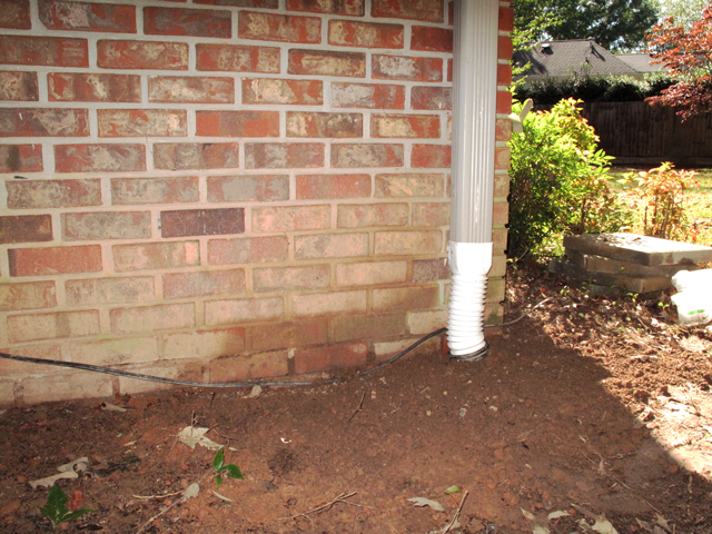 Soil is filled in around the newly  installed ground level downspout adapter that is attached to the now underground flexible drainpipe