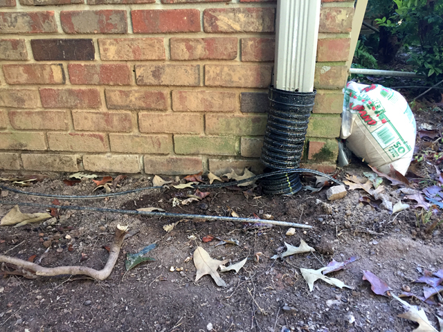 Corner of brick house where the rain barrel will be installed into downspout