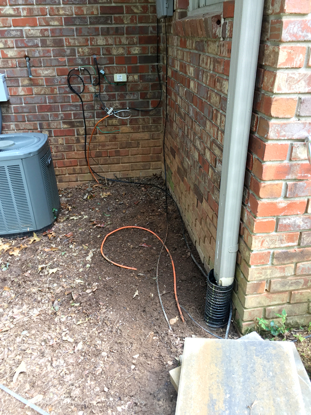 Metal downspout at corner of house with broken black flexible drain pipe at ground level