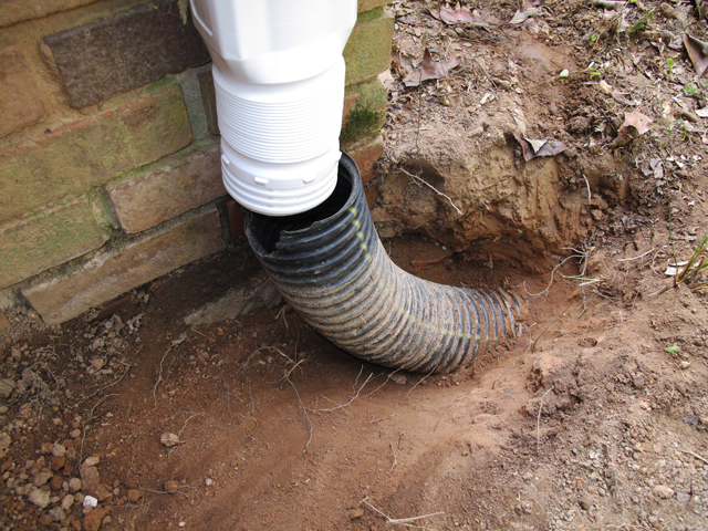 white downspout adapter is added to metal downspout and it hangs above the broken flexible drainpipe waiting to be connected