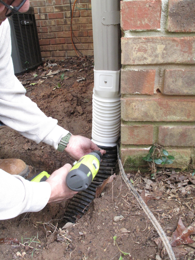 Screws are installed with a drill in order to secure the downspout adapter and the black flexible drainpipe in place