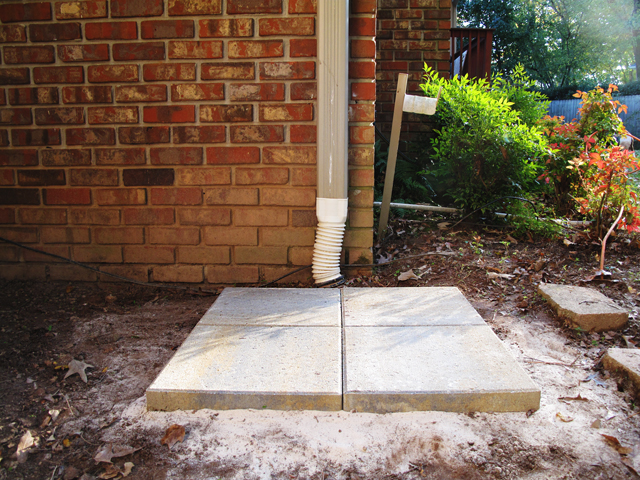 Ground level beneath the downspout shows all four concrete pavers in place