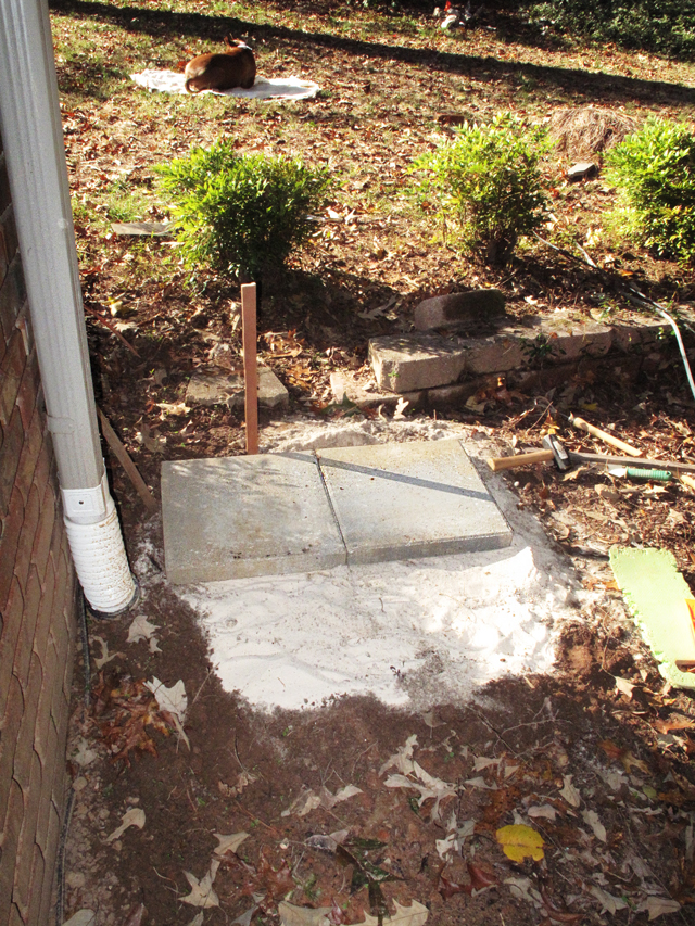 Ground level area beneath the downspout now has a layer of sand laid and 2 of 4 pavers are in place