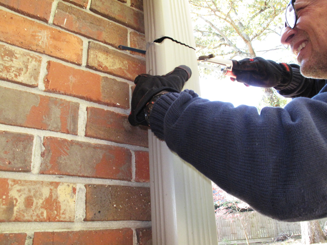 Man continues to saw the remainder of the downspout in order to remove the section in order to install the downspout diverter