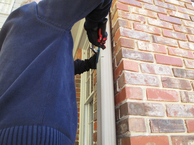 A hand saw is being used to cut through the downspout in order to remove a piece to make space for the diverter