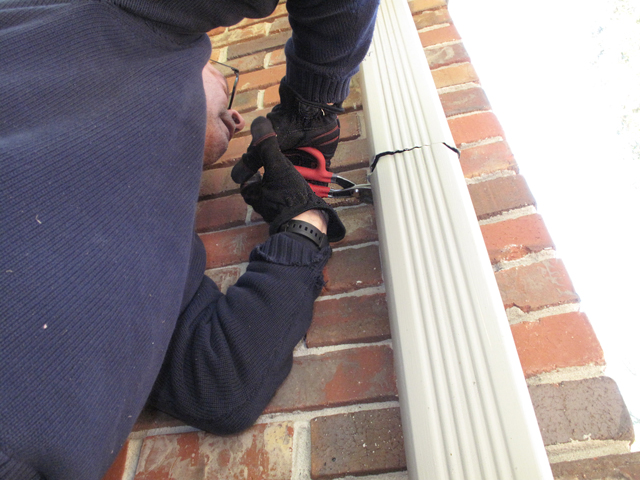 Tin snips are being used on the house downspout where the saw is not effective