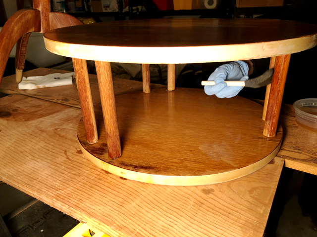 Bleach solution is applied with a sponge to wood supports between table shelves