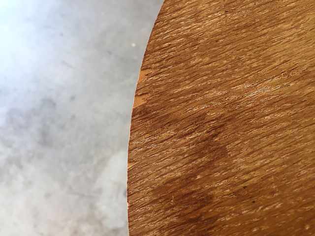 close-up view of wood tabletop showing light and dark areas and dust in crevices