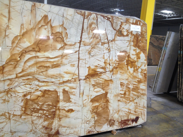 Large slab of stone with abstract brown patches on white marble background