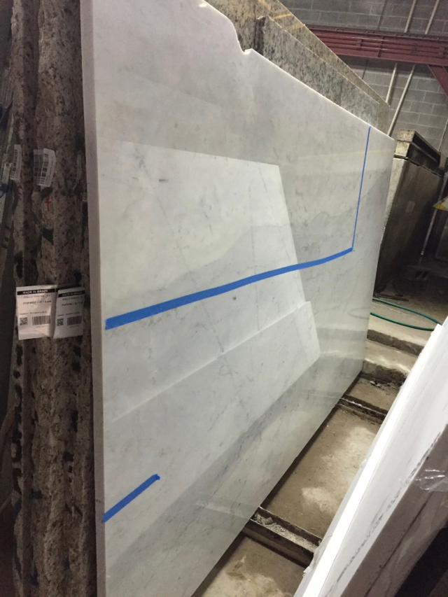 Large slab of white marble is marked with tape to indicate where cuts are to be made