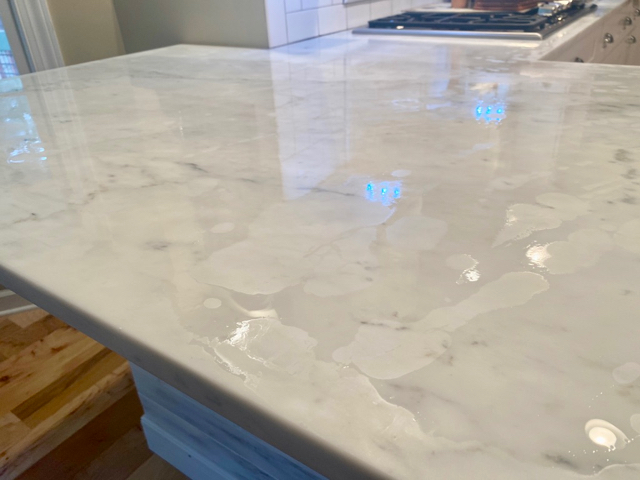 White marble countertop has liquid sealant on it with random light patches indicating areas of  absorption