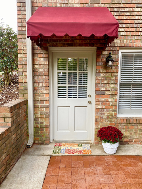 cleaned, red awning over door with colorful welcome mat and to of red mums